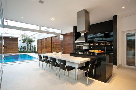 Piscina em frente a varanda com uma cozinha gourmet em preto e branco.