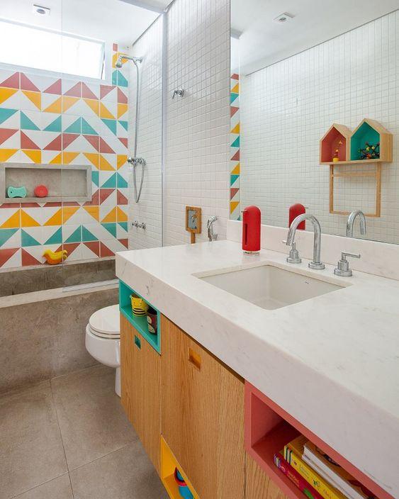 Banheiro decorado com nichos coloridos e parede principal com azulejos branco, amarelo, azul e vermelho.