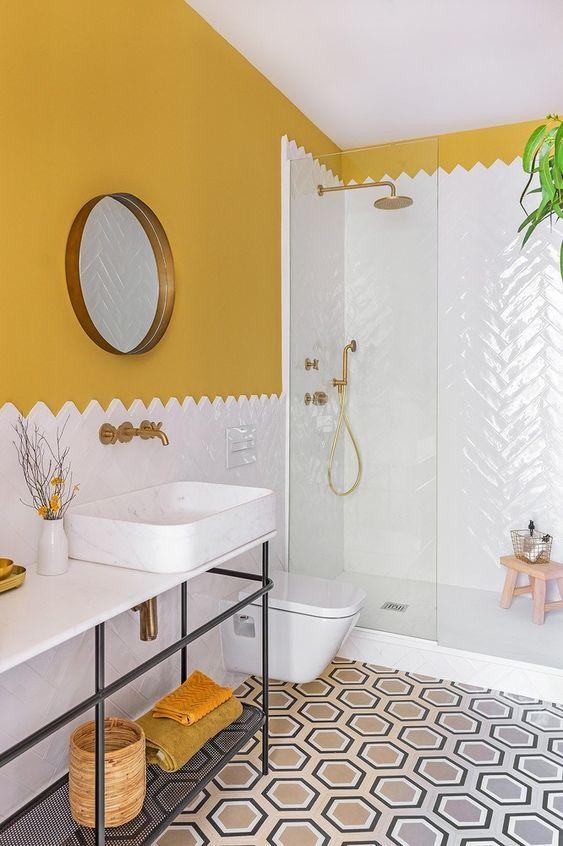 Banheiro branco e amarelo com revestimento em pequenos azulejos encaixados e piso com formas geométricas.
