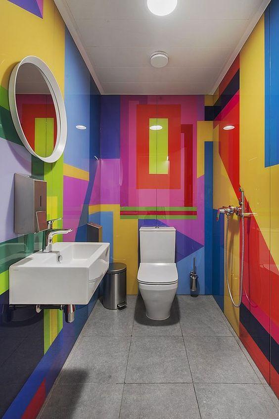 Banheiro decorado com apenas pia, vaso e espelho e com as paredes todas em mosaico grande colorido.