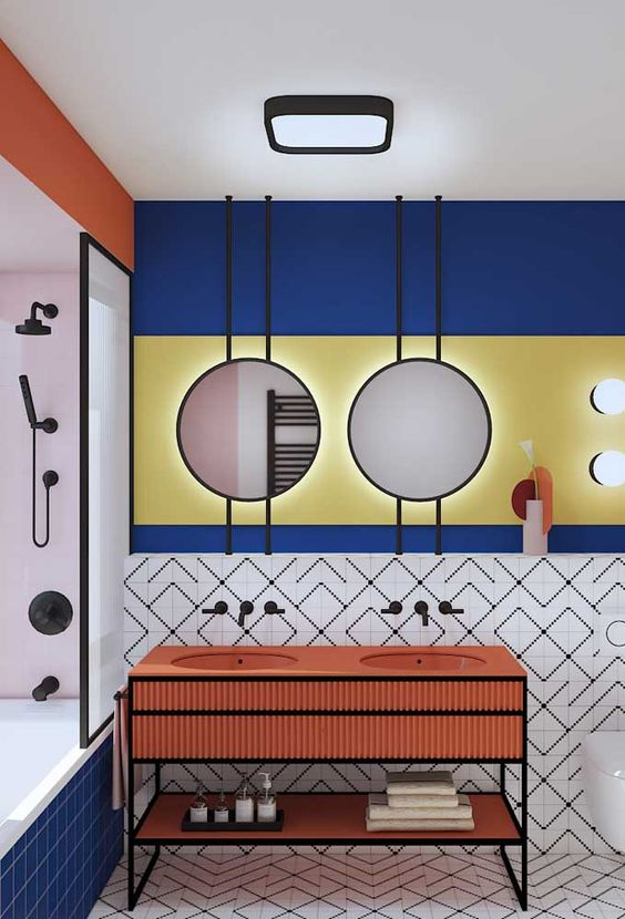 Banheiro duplo com duas pias e depois espelhos redondos. A parede é azul, amarela e branca com formas geométricas.