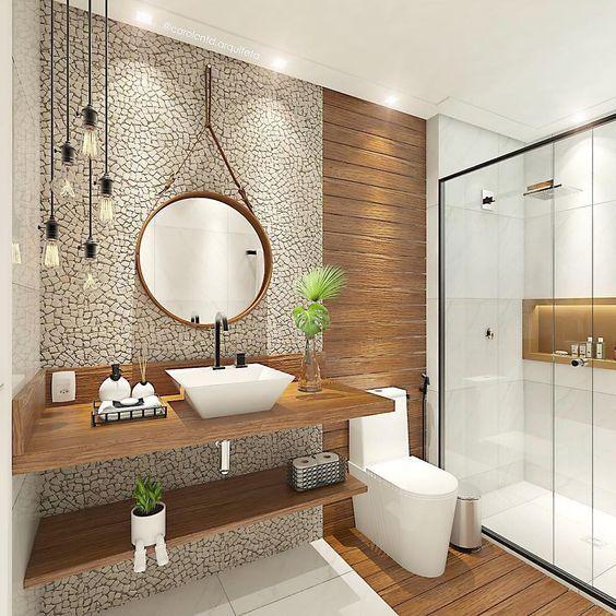 Banheiro com detalhes de madeira com dois pequenos vasos de planta, um na pia e outro na prateleira embaixo.