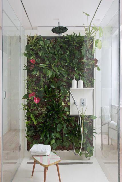 Banheiro decorado com parede inteira de folhagens e flores.