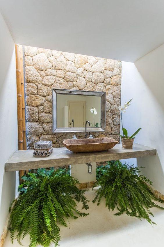 Banheiro decorado com dois grandes vasos de samambaia embaixo da pia e uma pequeno vaso de orquídeas em cima.