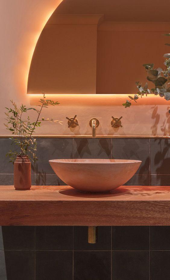 Banheiro decorado rosa com iluminação no espelho e pia embutida na parede.