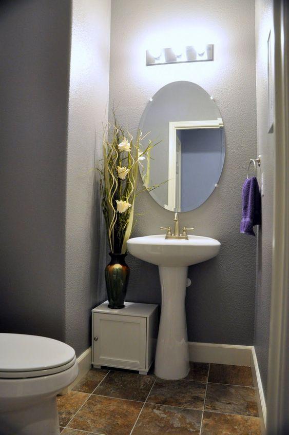 Banheiro decorado com vaso com planta artificial e que destaca em cômodo cinza e branco.