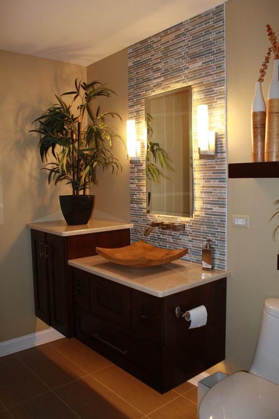 Banheiro decorado com vaso de planta no mesmo tom de marrom dos armários.