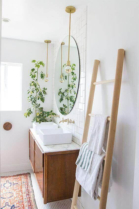 Banheiro decorado com planta cumprida que destaca na pia branca.