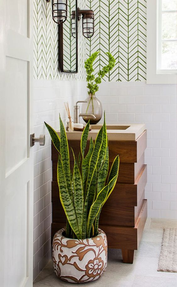 Banheiro com um vaso grande e decorado com folhagens no chão e um pequeno vaso de vidro na pia.