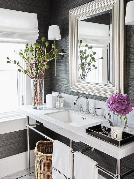 Banheiro com um vaso de flor roxa e outro com cactos, ambos em vasos de vidro na pia.