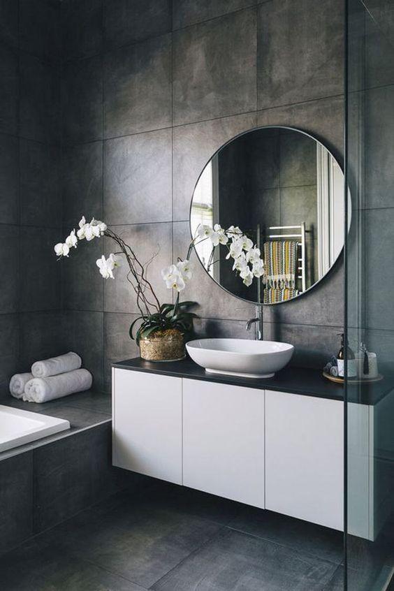 Banheiro decorado com orquídeas brancas que combinam com a pia, o armário, a banheira e as toalhas.