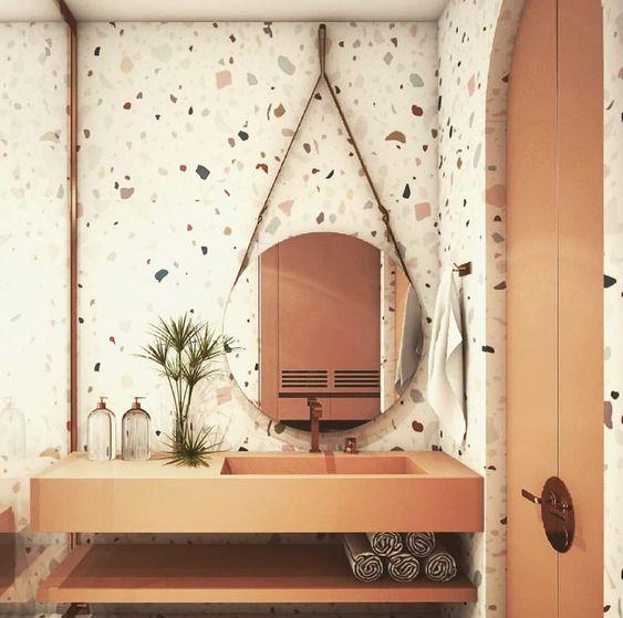 Banheiro todo revestido com azulejos manchados coloridos e pia, porta e prateleiras nas cores bronze.