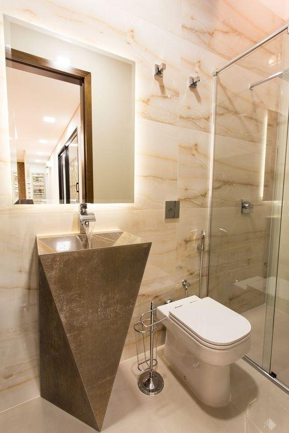 Banheiro decorado com pia e base feitas de mármore como peça única.
