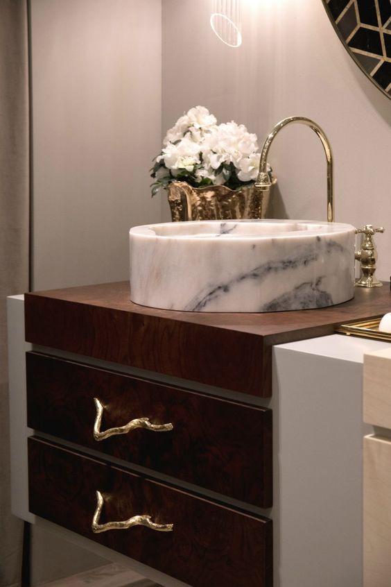 Cuba redonda feita de mármore branco manchado e torneira real dourada.