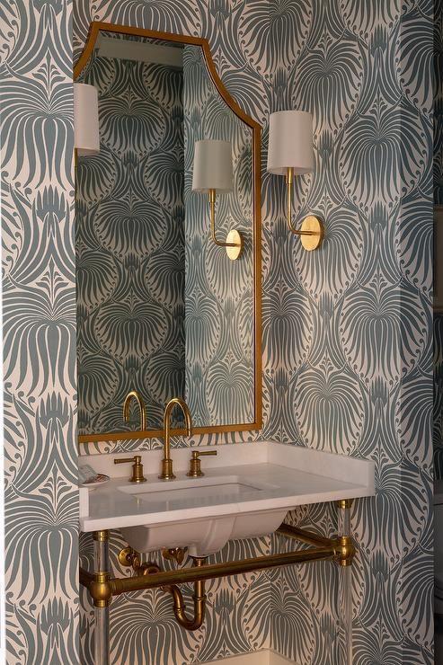 Banheiro decorado com pia branca e torneira dourada combinando com o encanamento e a moldura do espelho.