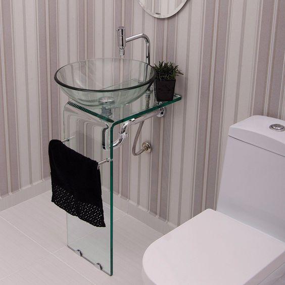 Banheiro decorado com cuba e apoio de vidro com suporte para toalha de mão.