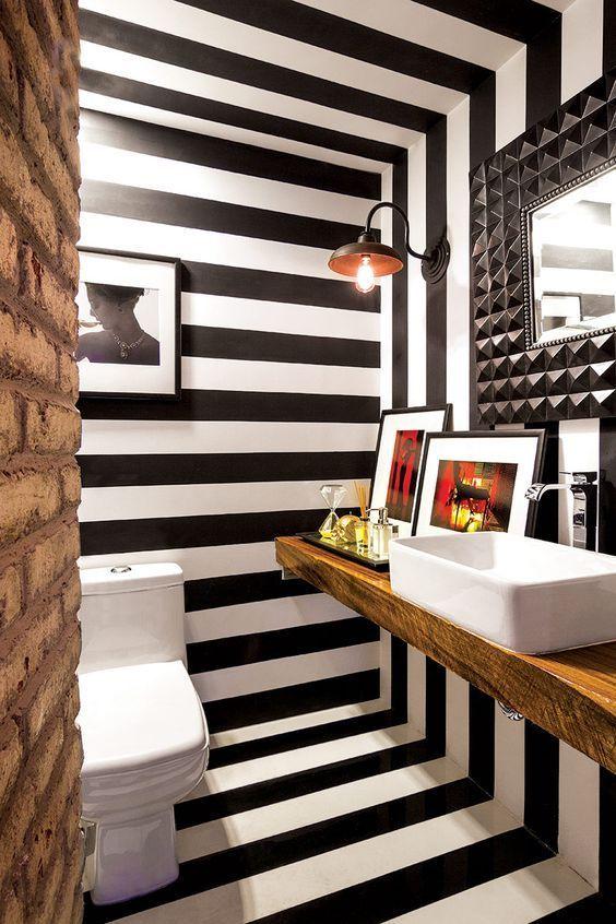 Banheiro decorado com listras pretas e brancas nas paredes, no teto e no chão.