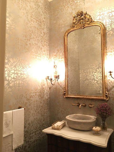 Banheiro decorado com espelho com bordas arredondadas e moldura clássica.