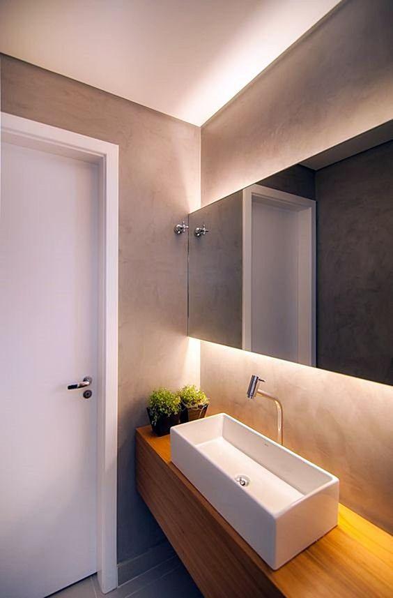 Banheiro decorado com espelho horizontal e luz embutida.