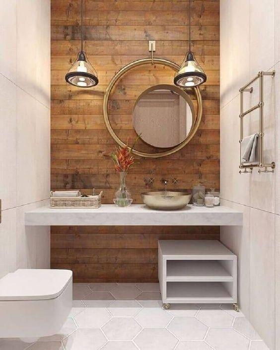 Banheiro decorado com espelho redondo e moldura grande suspensa por um gancho.
