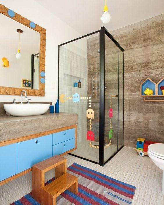 Banheiro infantil colorido com nichos organizadores e adesivos no box.
