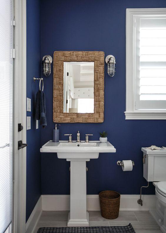 Banheiro decorado com espelho e moldura em madeira.