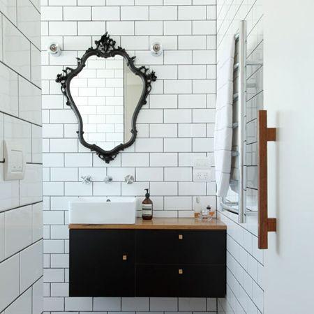 Banheiro decorado com espelho e moldura preta que constrasta com a parede branca.