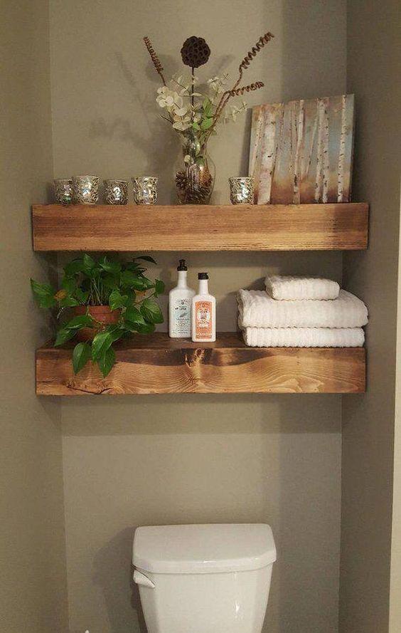 Banheiro decorado com duas prateleiras grossas de madeira com toalhas, plantas e artigos decorativos.