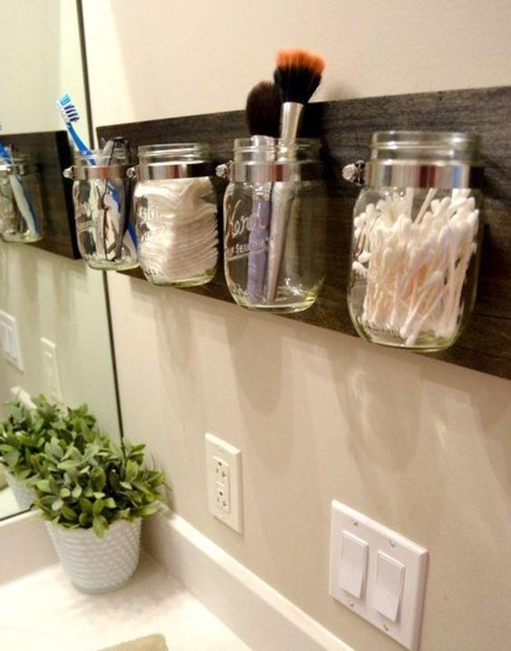 Banheiro decorado e organizado com portes de vidro fixados em uma tábua.