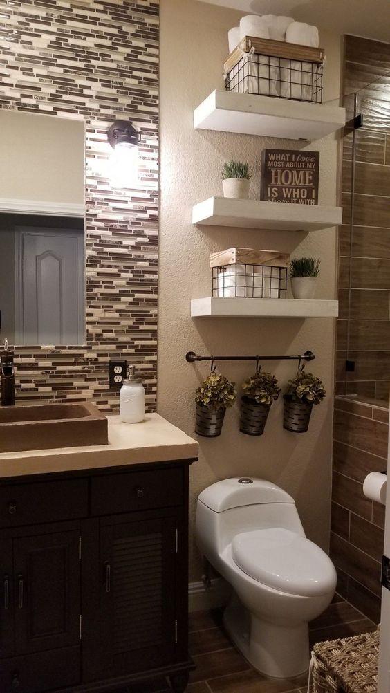 Banheiro com cestos para guardar papel higiênico e uma barra com ganchos para pendurar pequenas plantas.