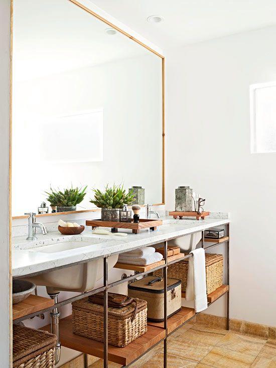 Banheiro decorado e organizado com prateleiras e cestos na mesma cor.