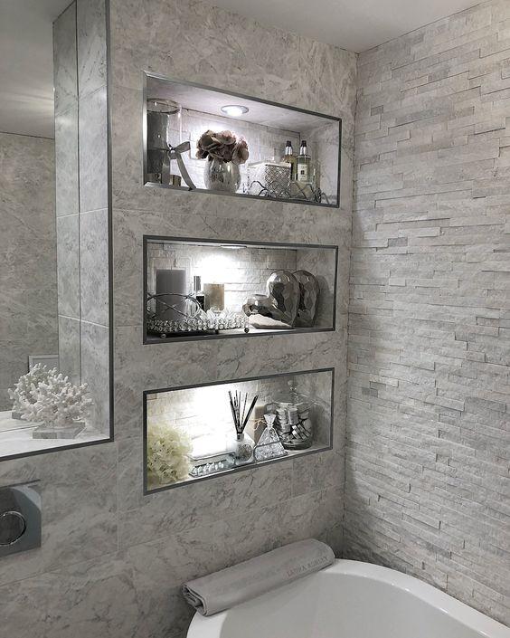 Três nichos iluminados embutidos ao lado da banheira.