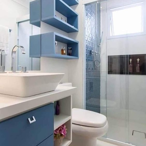 Banheiro decorado com parede de pastilhas, nichos e gavetas azuis.