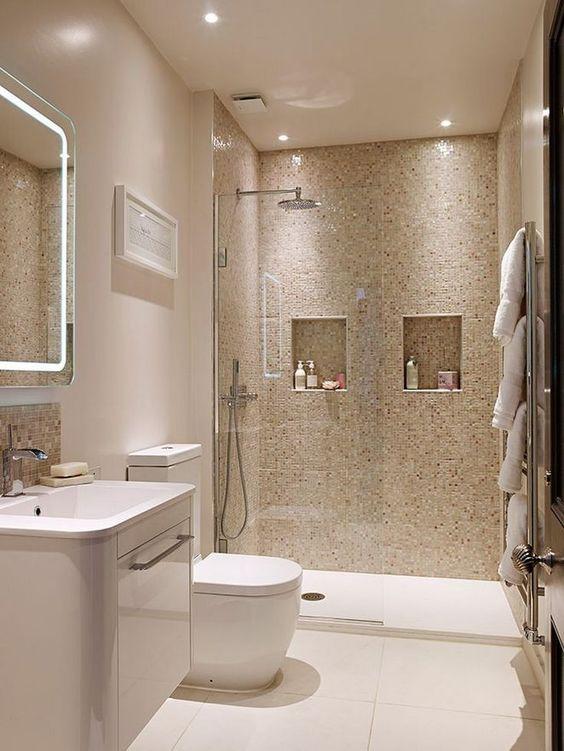 Banheiro decorado com dois nichos embutidos em uma parede de pastilhas.