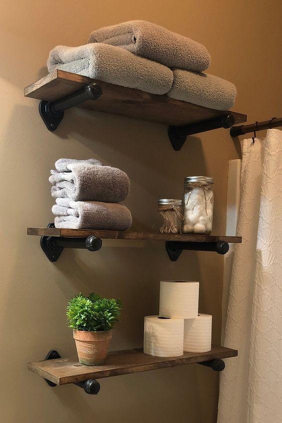 Banheiro decorado com três prateleiras de madeira com toalhas, potes organizadores, papel higiênico e vasinho de planta.