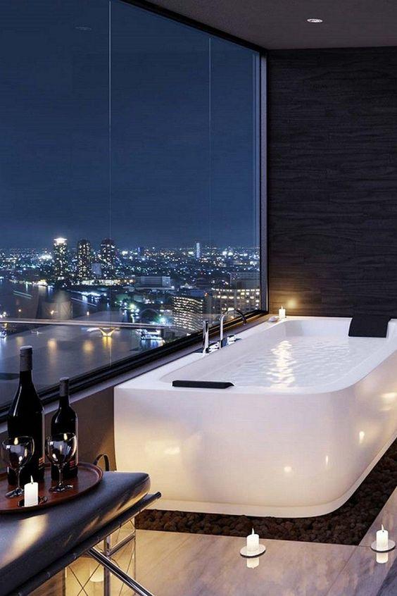 Banheiro decorado com banheira branca em base preta ao lado de uma janela com vista para cidade.