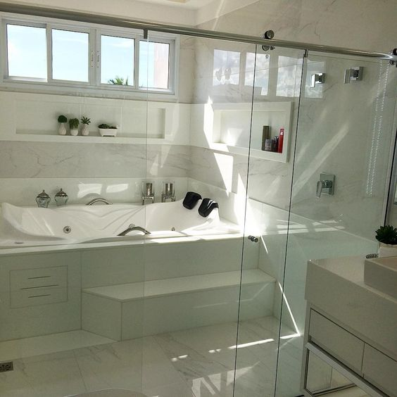 Banheiro decorado com hidromassagem de casal com nichos brancos embutidos na parede.