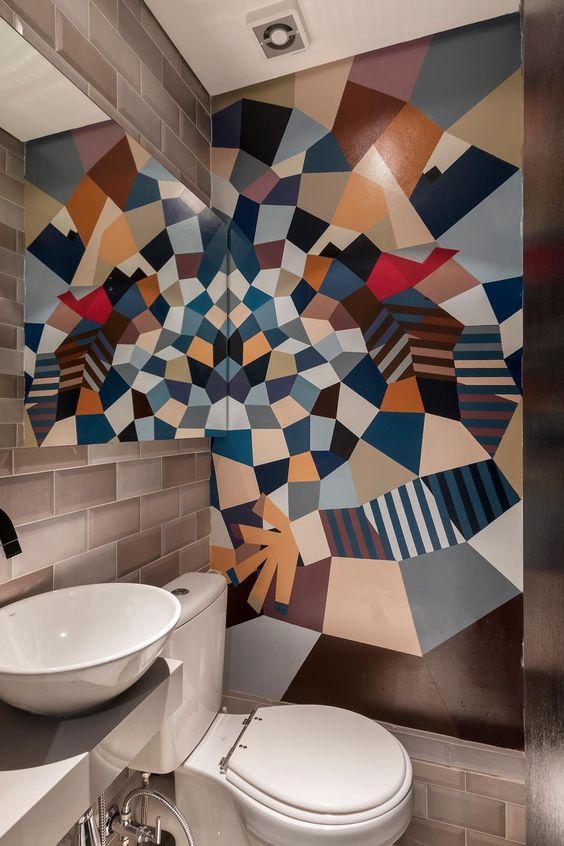 Parede única com mosaico feito de cores apagadas como marrom, azul marinho e bege.