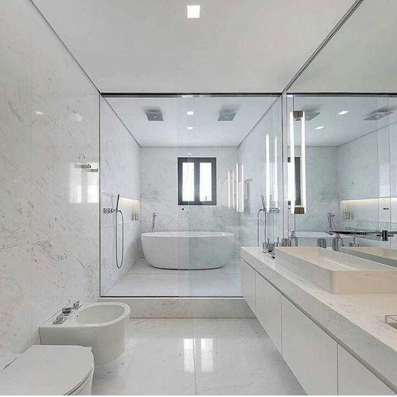 Banheira branca, oval dentro do bom ao lado da ducha.