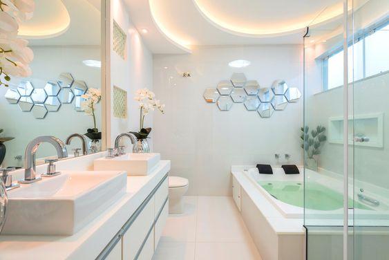 Banheiro decorado com banheira grande de casal ao lado do box com chuveiro.