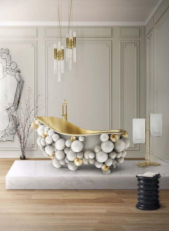 Banheiro decorado com banheira exótica com bolas cinzas e douradas.