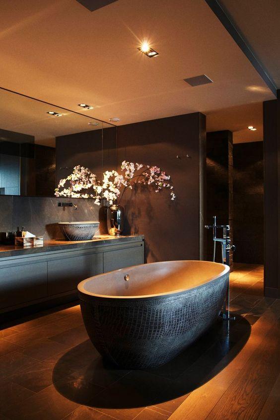 Banheiro decorado com banheira preta por fora com desenho que imita pele de cobra.