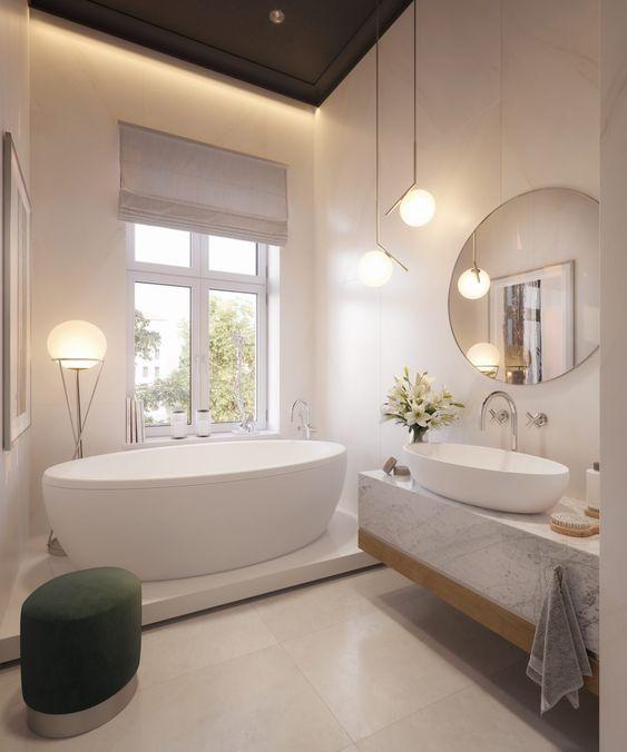 Banheira oval branca com abajur alto ao lado.