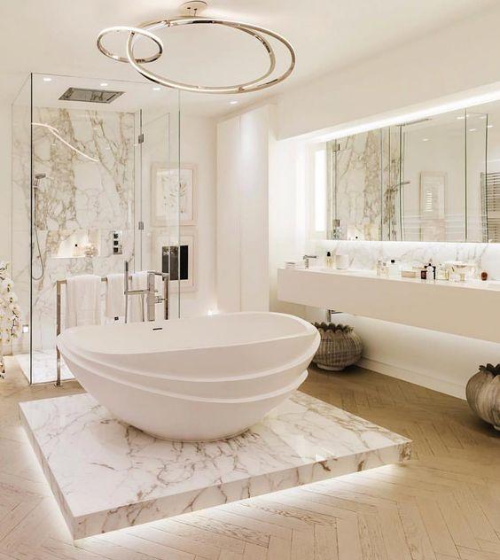 Banheira branca no centro do banheiro com base de mármore.
