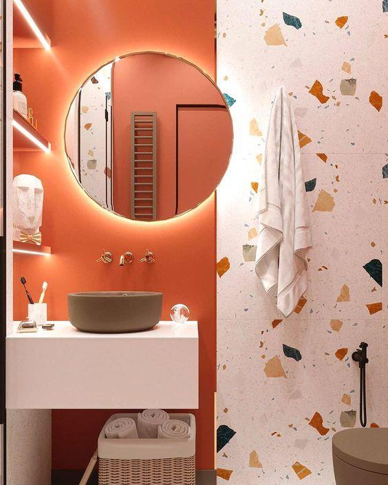 Banheiro decorado com parede metade avermelhada e metade com pisos manchados coloridos.