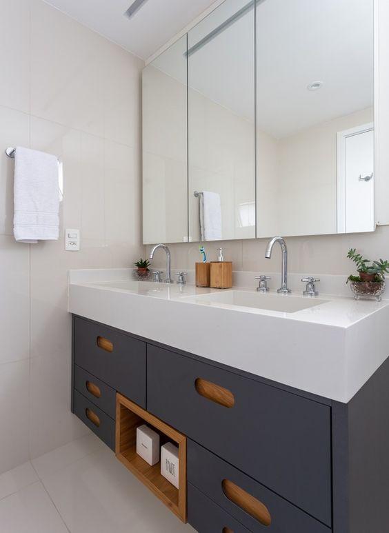 Pia branca com duas torneiras e armário em azul marinho.