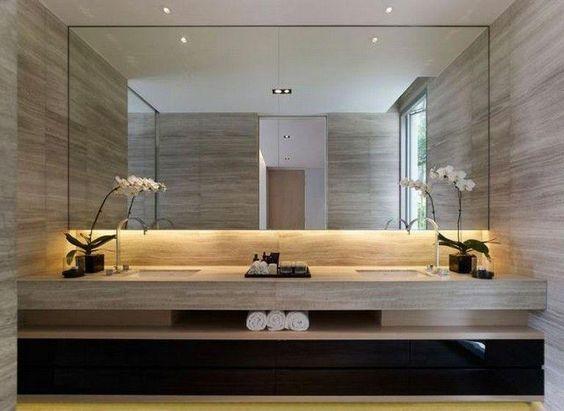 Banheiro decorado com duas pias e um grande espelho horizontal que vai de um lado ao outro na parede.