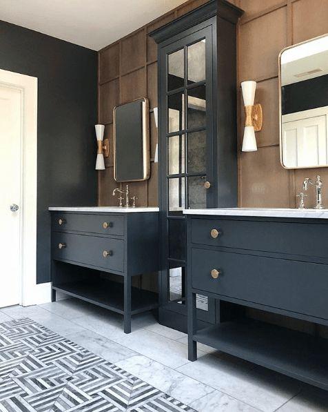 Banheiro decorado com duas pias e armários separados por um armário cumprido azul marinho.