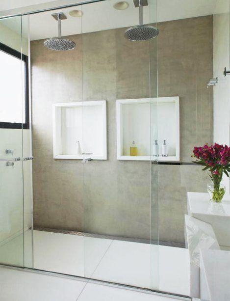 Banheiro decorado com dois chuveiros suspensos e nichos brancos separados.