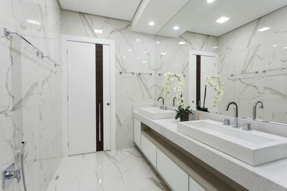 Banheiro decorado com duas pias e uma orquídea no meio.